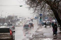 拉脱维亚,里加- 12月1 2017年:在城市、交通和人民的湿雪在溜滑街道上 免版税图库摄影