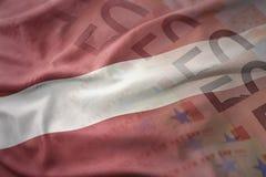 拉脱维亚的五颜六色的挥动的国旗欧元金钱钞票背景的 免版税库存照片