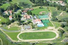 维拉诺瓦有轨道、水池、内野、网球场和校园的预科学校春天鸟瞰图视线内, Ojai,加州 免版税库存图片
