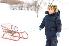 拉雪撬的逗人喜爱的小的男孩 库存图片