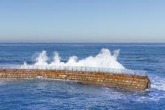 拉霍亚有碰撞的波浪的防波堤 免版税库存图片