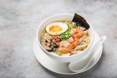 拉面面条汤用大虾、椎茸mushroms和鸡蛋在白色 免版税库存图片