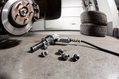 拉紧轮胎的气枪在一辆暂停的汽车闩上在一家汽车修理店 免版税库存图片