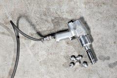拉紧轮胎的气枪在一辆暂停的汽车闩上在一家汽车修理店 库存图片