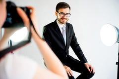 拍一个模型的照片摄影师在演播室 免版税图库摄影
