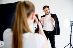 拍一个男性模型的照片女性摄影师在演播室 库存照片