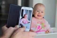 拍一个婴孩的照片有一个手机的 图库摄影
