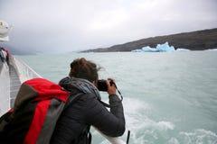 拍一座冰山的照片的小船的游人在阿根廷 免版税图库摄影
