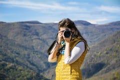 拍一座美丽的山的照片的少妇摄影师 免版税库存图片