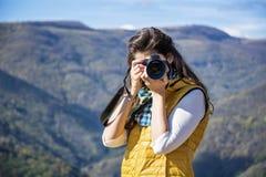 拍一座美丽的山的照片的少妇摄影师 库存图片