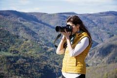 拍一座美丽的山的照片的少妇摄影师 库存照片