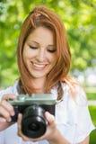 拍一张照片的俏丽的红头发人在公园 免版税图库摄影