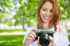 拍一张照片的俏丽的红头发人在公园 库存图片