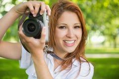 拍一张照片的俏丽的红头发人在公园 免版税库存图片