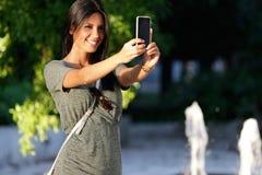 拍一张selfie照片的愉快的美丽的女孩在公园 免版税库存照片