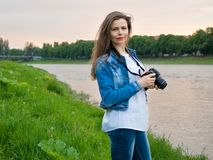 拍与一台专业照相机的棉花夹克的美丽的女孩游人照片在河的河岸刮风的天气的 库存图片