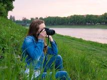 拍与一台专业照相机的棉花夹克的美丽的女孩游人照片在河的河岸刮风的天气的 免版税库存图片