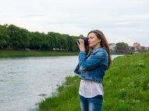 拍与一台专业照相机的棉花夹克的美丽的女孩游人照片在河的河岸刮风的天气的 免版税图库摄影