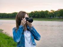 拍与一台专业照相机的棉花夹克的美丽的女孩游人照片在河的河岸刮风的天气的 库存照片