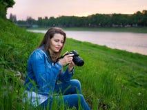 拍与一台专业照相机的棉花夹克的美丽的女孩游人照片在河的河岸刮风的天气的 免版税库存照片