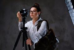拍与一台数字照相机的女性照片在三脚架 库存照片