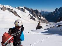 拍与一台照相机的登山家照片在山 免版税库存图片