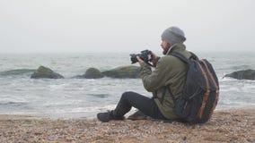 拍与专业照相机的有胡子的人照片在海洋前面 影视素材