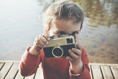 拍与减速火箭的照相机的男孩照片 免版税库存照片