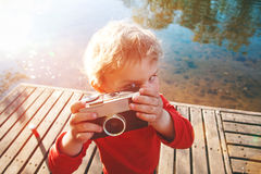 拍与减速火箭的照相机的男孩照片 免版税库存图片