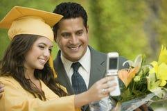 拍与外面手机的毕业生和父亲照片 免版税库存照片