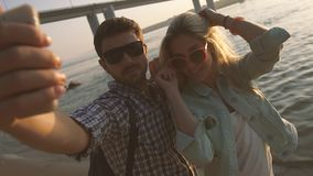 拍与外面手机的年轻愉快的夫妇照片在海滩 影视素材