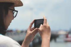拍与她巧妙的电话的旅游妇女照片 库存图片