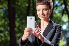 拍与她的手机照相机的年轻短发妇女一张照片 免版税库存图片