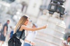 拍与她的手机的俏丽的旅游少年一张照片 酸碱度 免版税库存照片
