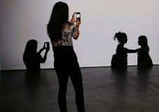 拍与她的智能手机的女孩照片 免版税库存照片