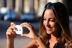 拍与她的智能手机的年轻和俏丽的妇女照片 免版税库存图片