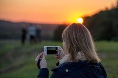 拍与她的电话照相机的妇女照片 免版税库存图片
