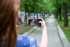 拍与她的电话的少妇一张照片 免版税图库摄影