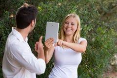 拍与她的男朋友数字式片剂的少妇照片  免版税库存图片