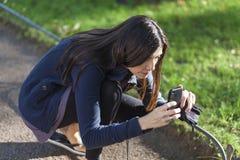 拍与她的smarphone的美丽的妇女照片在公园 免版税库存图片