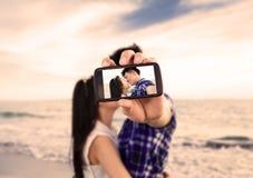 拍与巧妙的电话的夫妇自画象照片 免版税库存照片