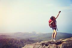 拍与巧妙的电话的少妇远足者照片 库存图片