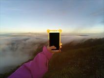拍与巧妙的电话的手照片在山峰 日出轻的口气 免版税图库摄影