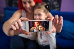 拍与手机妈妈和女儿的照片 免版税库存照片