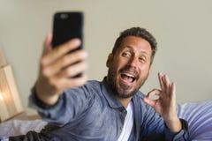 拍与手机微笑的嬉戏打手势的年轻可爱和愉快的30s或40s人生活方式画象selfie照片 免版税库存照片