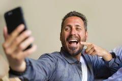 拍与手机微笑的嬉戏打手势的年轻可爱和愉快的30s或40s人生活方式画象selfie照片 免版税图库摄影