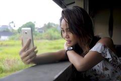 拍与手机照相机微笑的愉快坐的年轻美丽的亚裔女孩selfie照片户外在咖啡店 库存照片