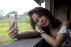 拍与手机照相机微笑的愉快坐的年轻美丽的亚裔女孩selfie照片户外在咖啡店 库存图片