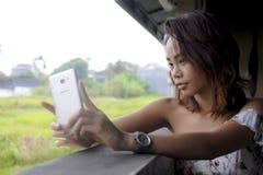 拍与手机照相机微笑的愉快坐的年轻美丽的亚裔女孩selfie照片户外在咖啡店 图库摄影
