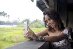 拍与手机照相机微笑的愉快坐的年轻美丽的亚裔女孩selfie照片户外在咖啡店 免版税库存图片